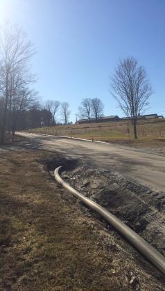 A manure hose runs through a culvert to get to the field.