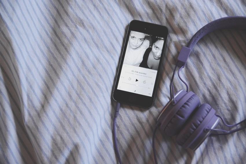 iphone med podcast som spelar och lila hörlurar på en säng lyssna på podcast bästa apparna för iphone android windows phone