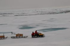 Sea Ice Physics Team Member Jakob Belter, and PhD Student Mia Hansen transporting equipment to the site.