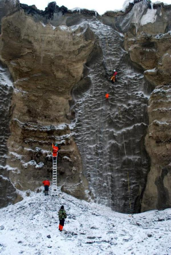 Breen (top right) collects ice samples every five vertical meters from the ice wedge on rappel during a trip to the North Slope of Alaska, to sample 30-m yedoma (organic-rich Pleistocene-age permafrost) exposure on the Itkillik River. (Photo by J. Strauss)