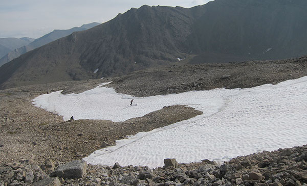 Tedesche (left) and field partner, National Park Service Archaeologist Chris Ciancibelli, collect fine scale GPS field data of a perennial snowfield's extent, to compare on-the-ground measurements with modeled extent derived from remotely sensed satellite information in the central Brooks Range, Northern Alaska. (Photo by R. Swisher)