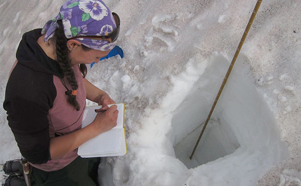 Molly Tedesche uses a test profile snow pit to determine physical structure and layering of snow crystals and ice lenses in the central Brooks Range, Northern Alaska. (Photo by C. Ciancibelli)