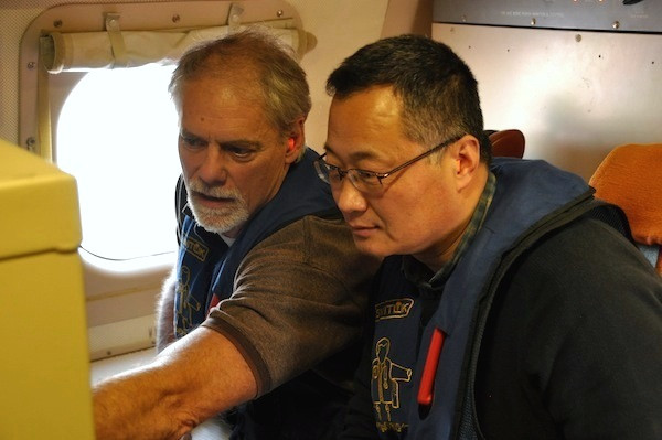 Xiangdong Zhang (right) and his colleague examine dropsonde observations on board the National Oceanic and Atmospheric Administration (NOAA) aircraft WP-3D, over the Chukchi Sea. A dropsonde was used to measure the atmospheric vertical profile. (Photo by M. Wang)