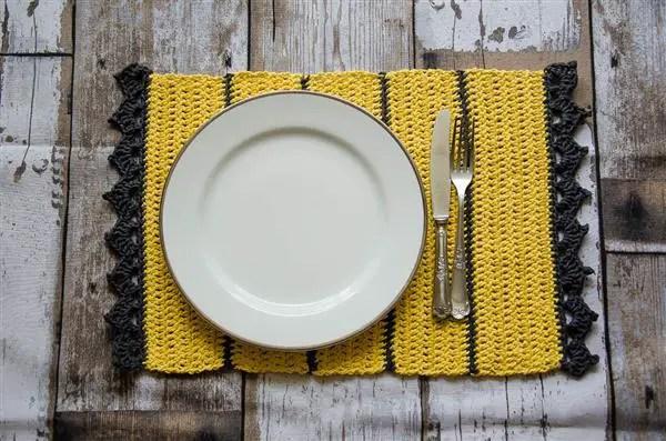 sousplat de crochê retangular amarelo e cinza com um prato e talheres em cima.