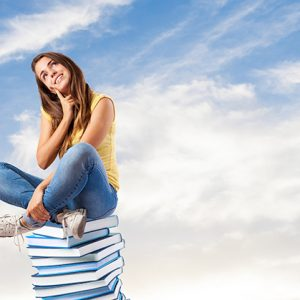 young pretty woman thinking and sitting on a big books pile