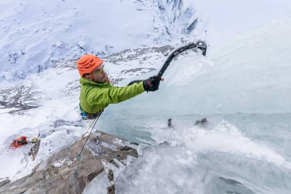Gros plan du planté de piolet d'un grimpeur sur glace au dessus de Chamonix