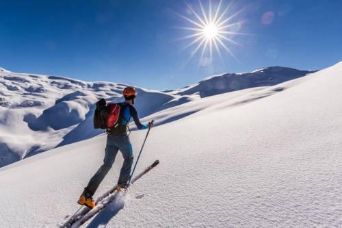 Illuminé Par Un Soleil Resplendissant, Un Skieur Fait Sa Trace De Montée Dans La Froide Poudreuse Du Beaufortain