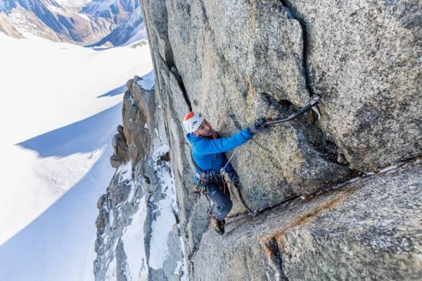 Un alpiniste gravit une voie difficile en face nord du Mont Blanc du Tacul au dessus de la Vallée Blanche