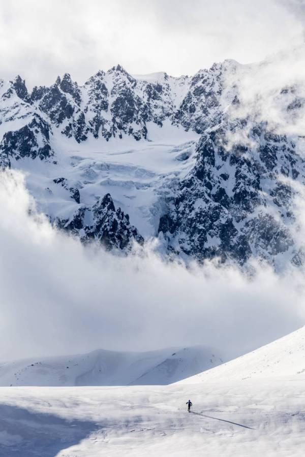 Un personnage semble perdu face à l'immensité de la face nord des Agneaux prise dans les nuages