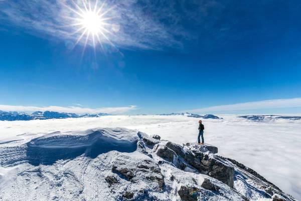 Un randonneur contemple la vallée du Grésivaudan sous une mer de nuage depuis le sommet de Chamechaude