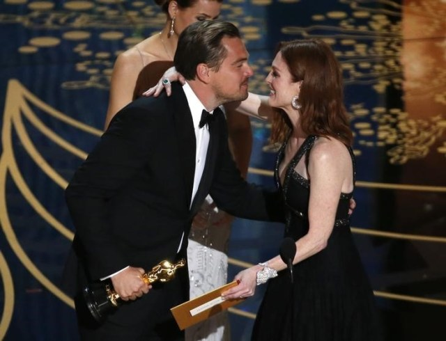 "Leonardo DiCaprio receives the Oscar for Best Actor for the movie ""The Revenant"" from Julianne Moore at the 88th Academy Awards in Hollywood, California February 28, 2016. REUTERS/Mario Anzuoni"