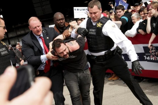 U.S. Secret Service agents detain a man after a disturbance as U.S. Republican presidential candidate Donald Trump spoke at Dayton International Airport in Dayton, Ohio March 12, 2016. REUTERS/William Philpott