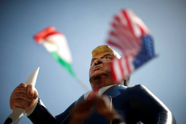 Mexican and U.S. flags are seen under an inflatable effigy of Republican presidential candidate Donald Trump during a march at an immigrant rights May Day rally in Los Angeles, California, U.S., May 1, 2016. REUTERS/Lucy Nicholson