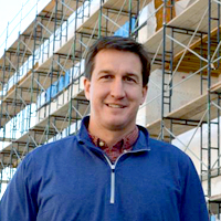 Portrait of UC-B Owner Lance Carlton: caucasian man in blue pullover in front of a construction site.