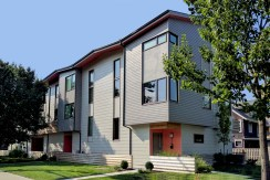 Exterior view of townhome complex : grey siding with orange doors with trees in front of builder.