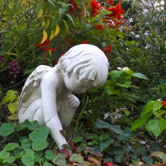 Garden statue of an angel appearing out of the Salvias