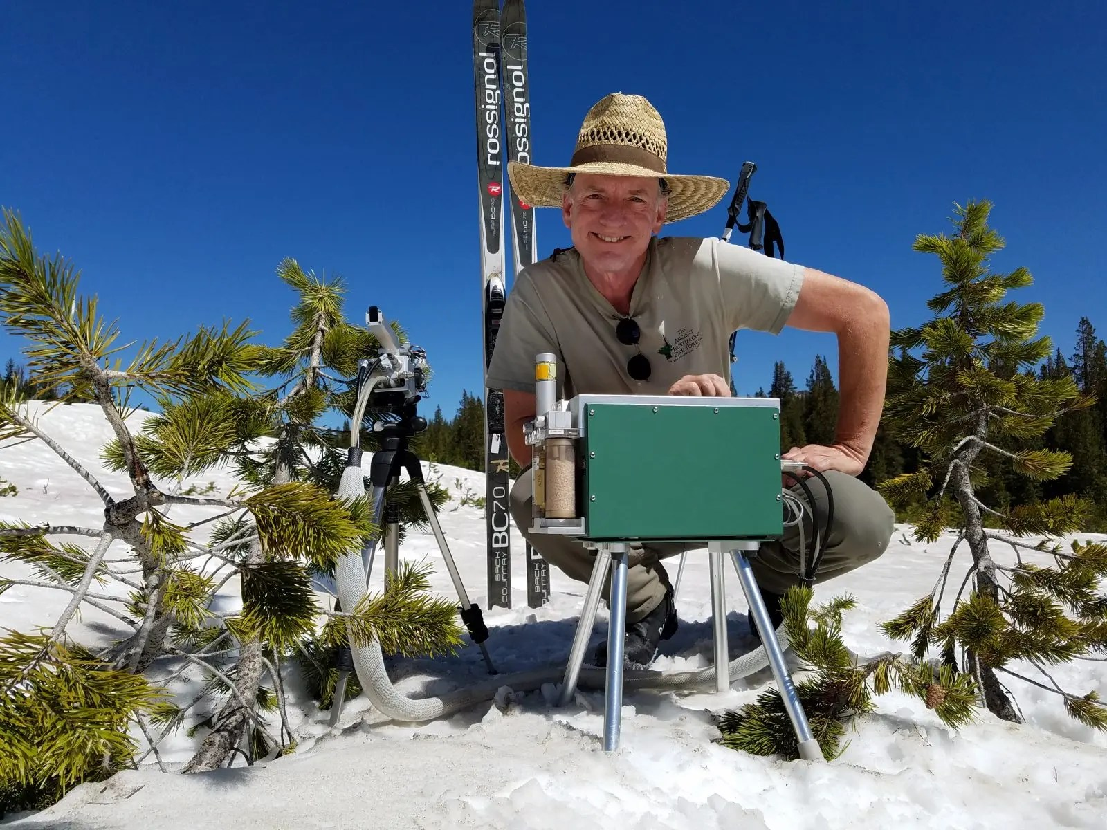 Loik next to his skis in snow with young pines by instruments he uses to study plant productivity