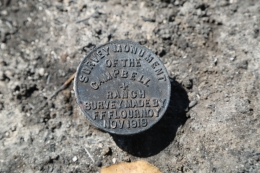 circular brass survey marker in rock