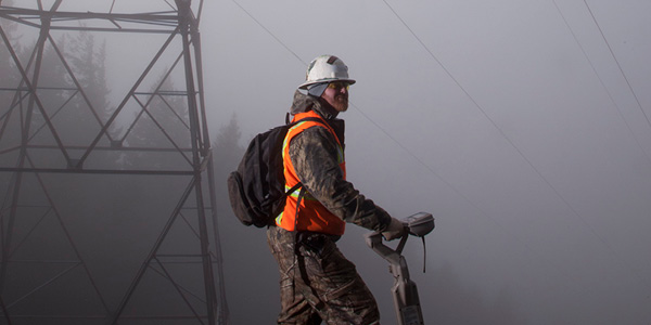 Utility worker near power line tower