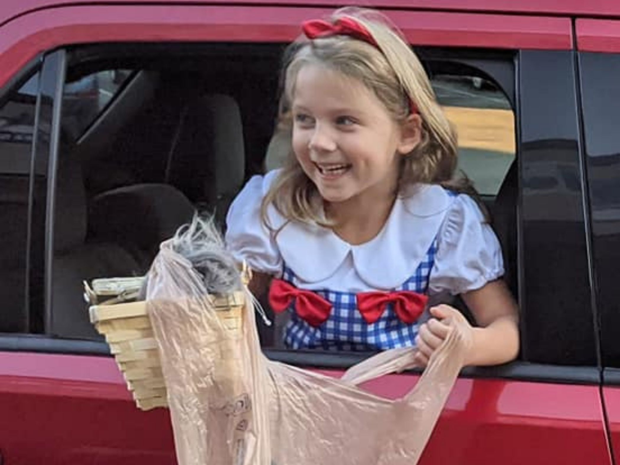 Child waits to get candy from car window