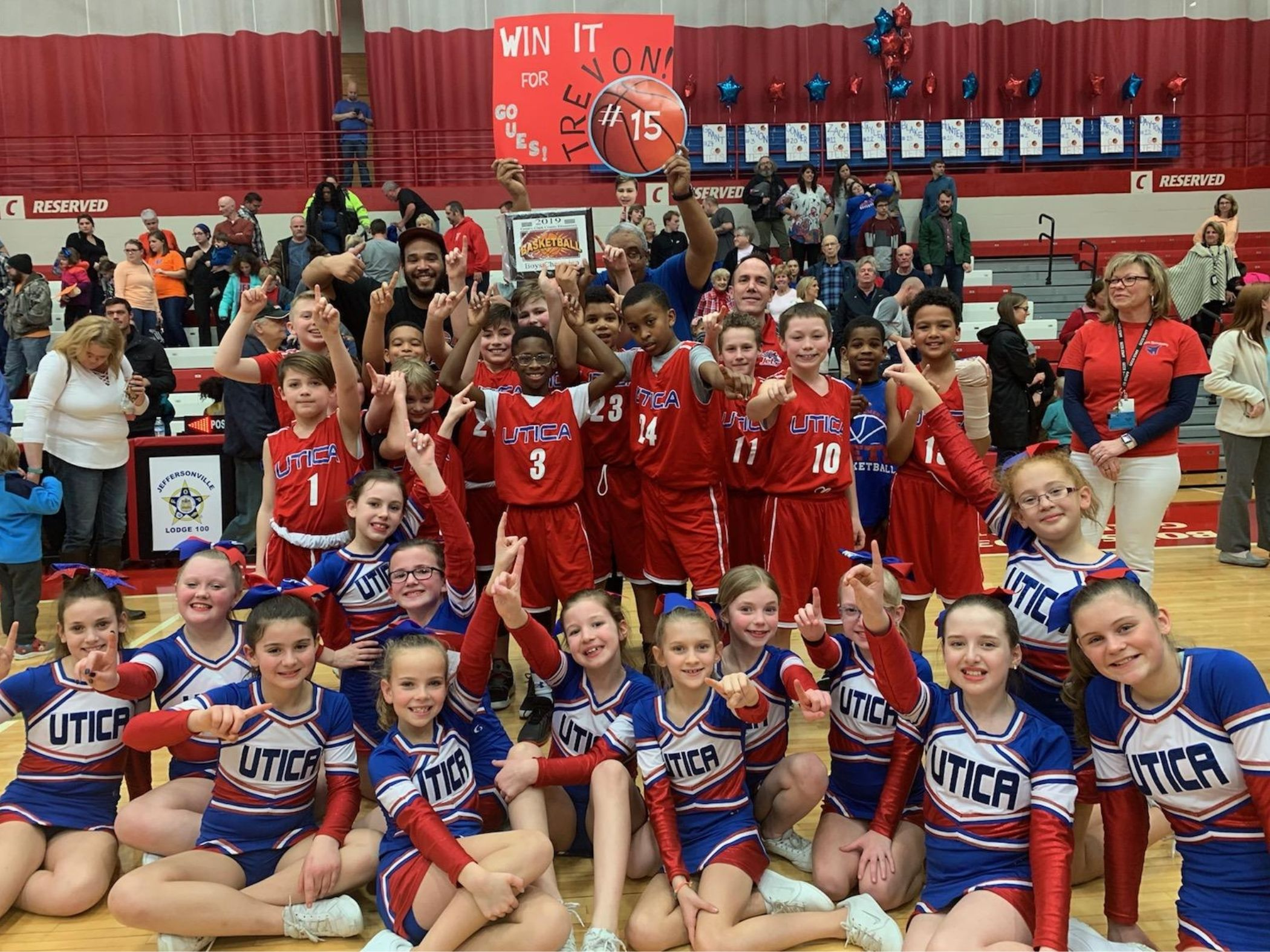 Winning basketball team poses with cheerleaders