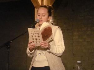 Den professionelle kropsvæskebeskriver Olga Ravn i færd med at oplæse manualen til kussomaten under et arrangement i KVINFO (Knus Vesten! Islamisér, Nedgør og Feminisér Overalt). Foto: Martin88berger