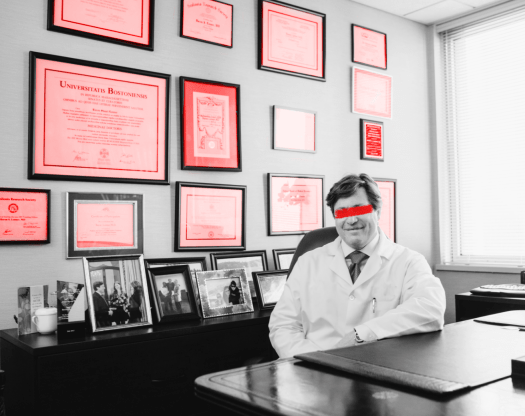 A doctor in an expensive office, its walls covered in diplomas. The doctor is grinning but his eyes are obscured by a slash of red paint.