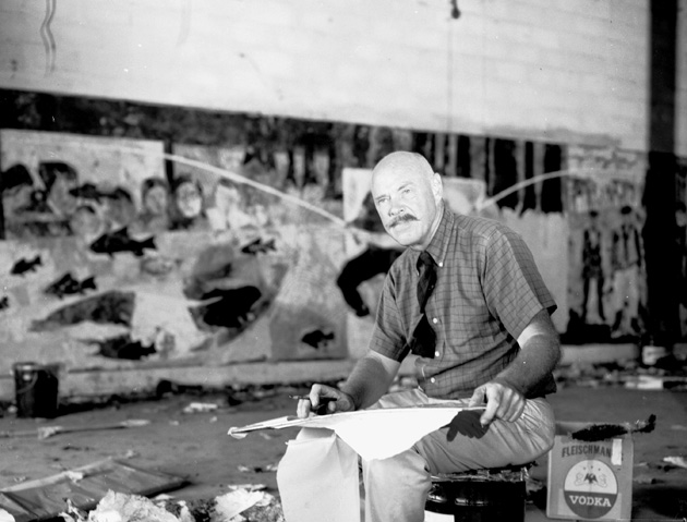 Man with tie sitting with paper on his lap. A mural is on the wall behind him.