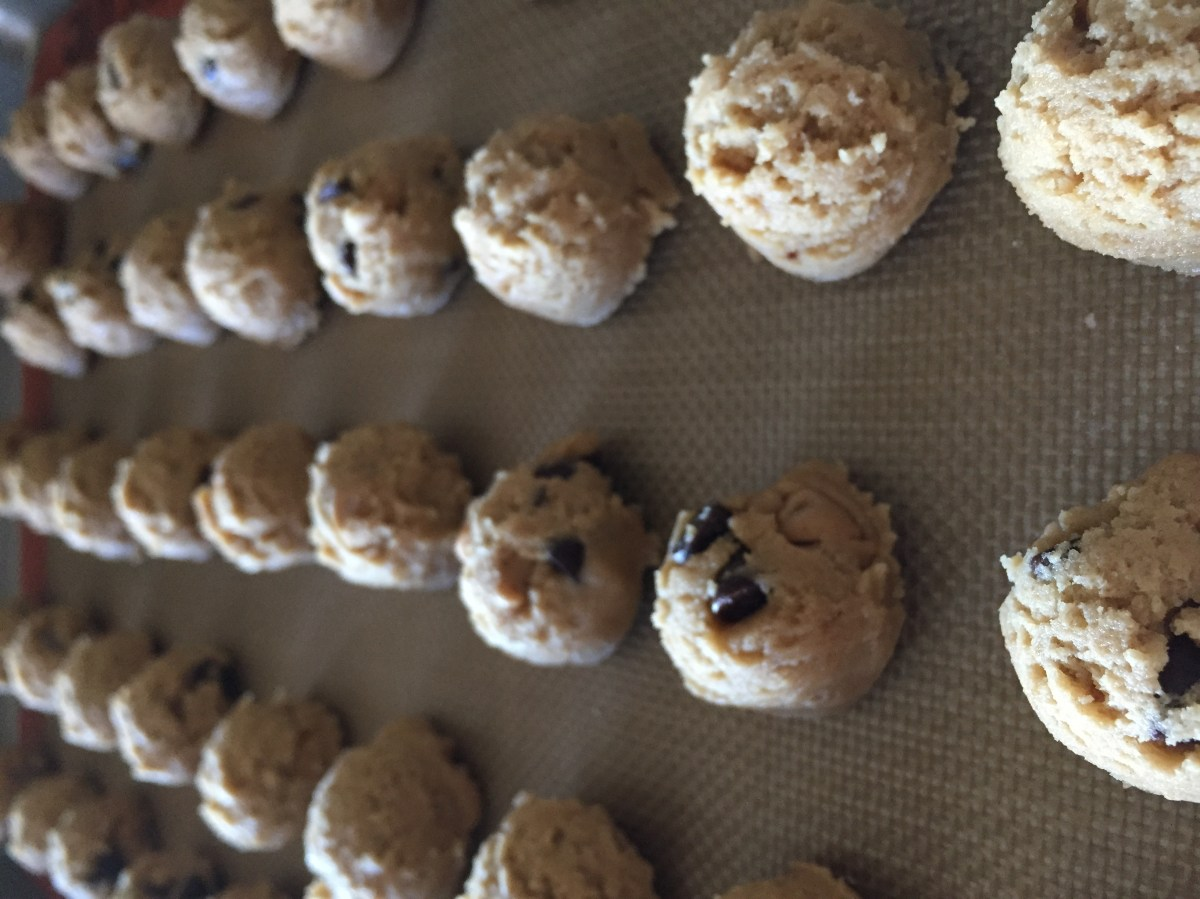 a tray of scoops of peanut butter chocolate chip cookie balls ready to go into the freezer