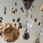 a picture of thick chocolate peanut butter cookies on a mirror with chocolate and peanut butter chips in glasses and scattered all around