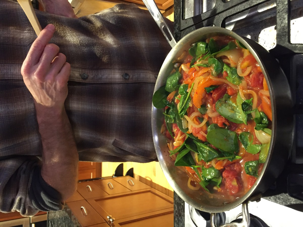 A pan with peppers, onions, tomatoes, and greens.