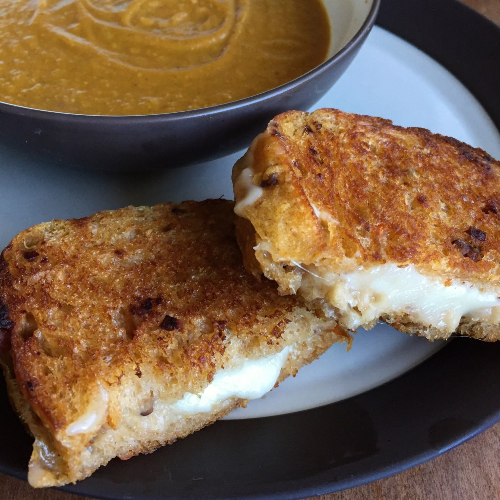 a grilled cheese sandwich and a bowl of soup