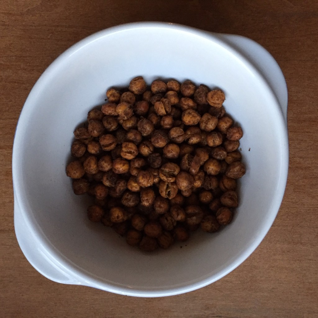 a bowl of pumpkin pie spiced chickpeas with a shallow falling in the bowl