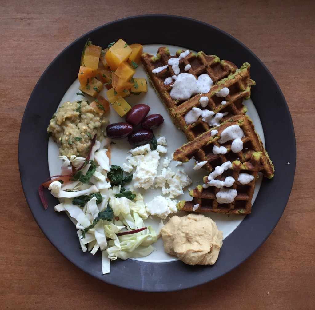 a plate of pita with sumac sauce, olives, roasted beets, baba ganoush, hummus, feta cheese, and coleslaw