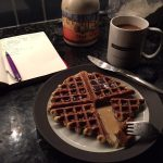 a plate of orange poppy seed waffle with fork, knife, and syrup alongside a coffee cup, syrup bottle, and a small notebook with a pen