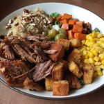 a bowl of pulled pork, cornbread croutons, corn and other vegetables