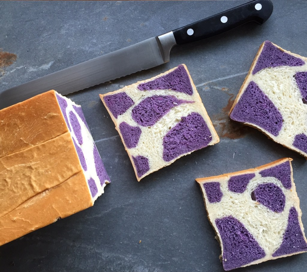 A loaf of purple cow print milk bread and three slices and a bread knife