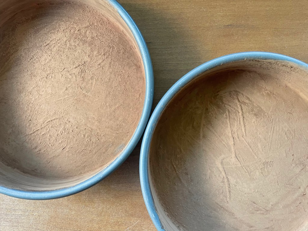 cake pans dusted with cocoa powder