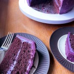 two slices of purple velvet cake and a cake