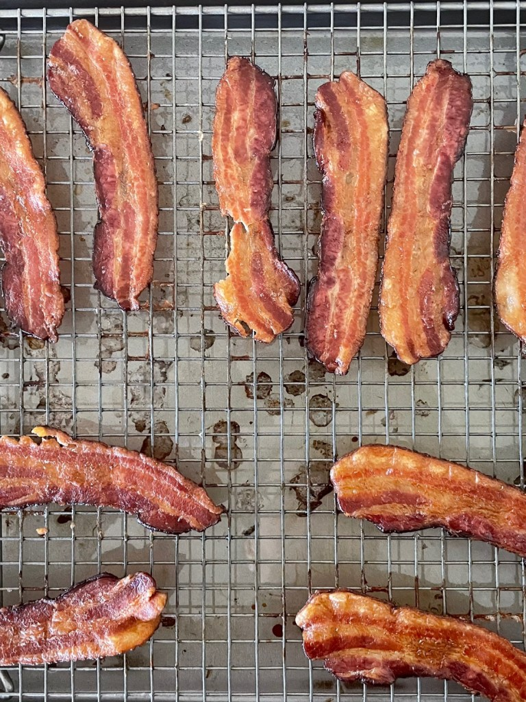 Twelve strips of cooked bacon on a baking rack in a baking sheet