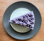 a slice of Earl Grey lavender cake with frosting piped into starsfrom the top