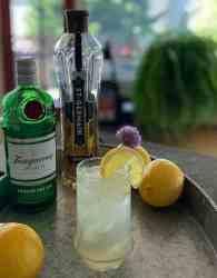 an elderflower Collins on a platter with a bottle of gin, a bottle of elderflower liquor, and three lemons
