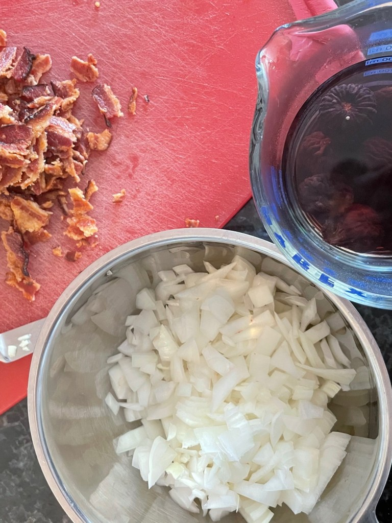 ingredients for fig bacon jam including chopped garlic and bacon on a cutting board, chopped onions in a bowl, and dried figs soaking in a measuring cup