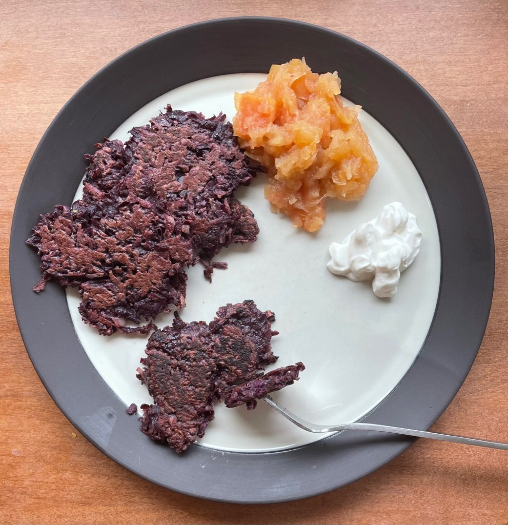 A plate with three purple sweet potato pancakes, homemade applesauce, and sour cream