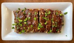 a white platter with sliced ground duck meatloaf garnished with chopped green onions