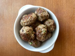 a bowl of lamb meatballs with sesame seeds, cumin, and coriander