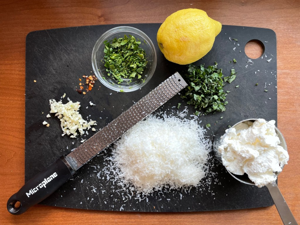 A cutting board showing the ingredients for one pot pasta with ricotta and lemon including chopped garlic, red pepper flakes, chopped parsley, a lemon, chopped basil, grated parmesan and a microplane, and a cup measure of ricotta cheese