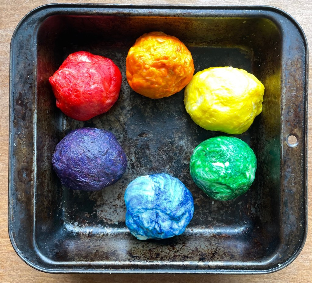 A pan with six balls of dough in the colors of the rainbow