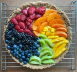 A rainbow fruit tart with strawberries, apricot, mango, kiwi, blueberries, and blackberries in a spiral pattern