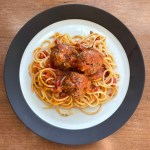 A plate of spaghetti with three braised meatballs in tomato sauce